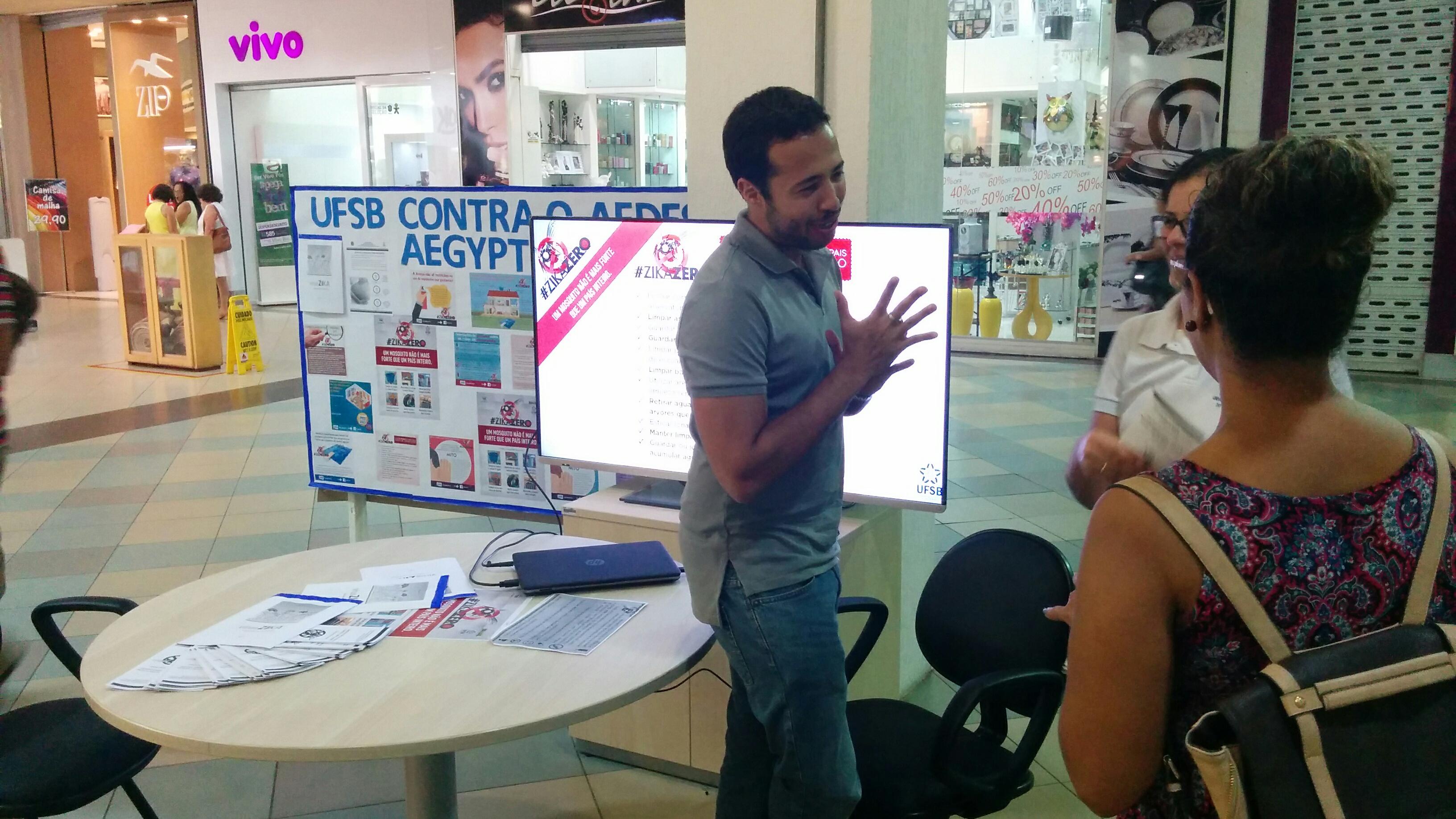 servidor da ufsb sorri e gesticula ao conversar com duas visitantes do shopping, que aparecem à direita na imagem