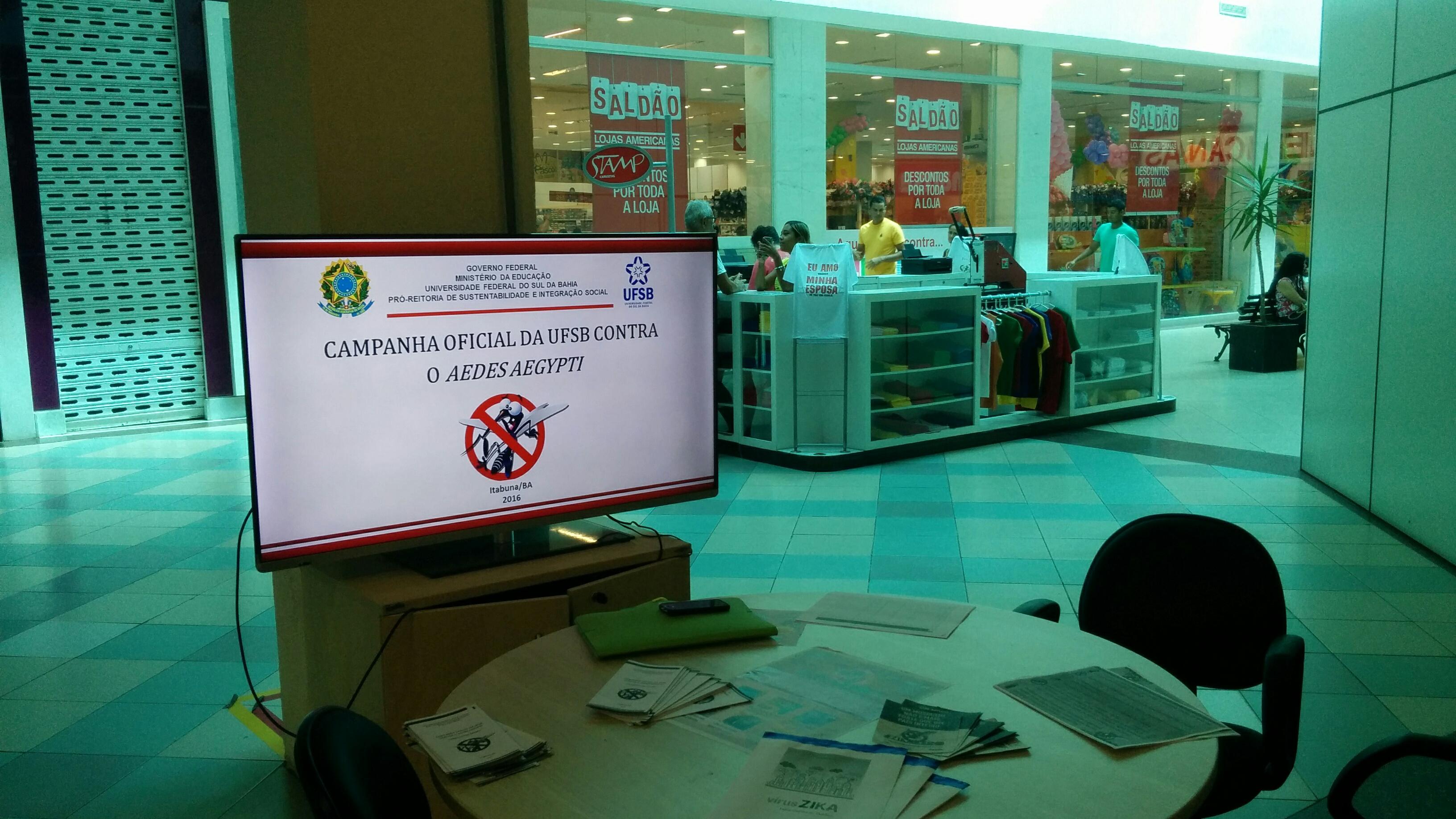 Tela do estande em primeiro plano, exibindo as informações da Campanha contra o mosquito vetor das doenças, com as vitrines das lojas próximas ao fundo