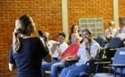 silvia aparece em primeiro plano, de costas para a câmera e segurando um microfone. ela fala para o público que aparece sentado no auditório, de frente para ela.
