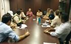 Diversas pessoas estão sentadas ao redor de uma mesa retangular. Ao fundo, o secretário de Desenvolvimento Urbano de Itabuna e a vice-reitora da UFSB estão à cabeceira da mesa.