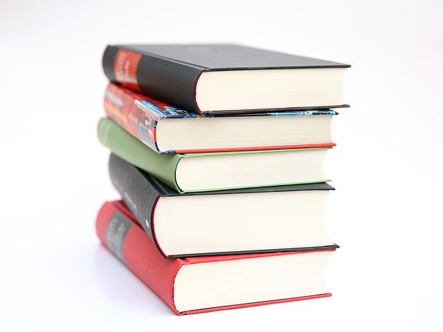 uma pilha de livros em cima de uma superfície branca. os livros possuem cores e tamanhos diferentes