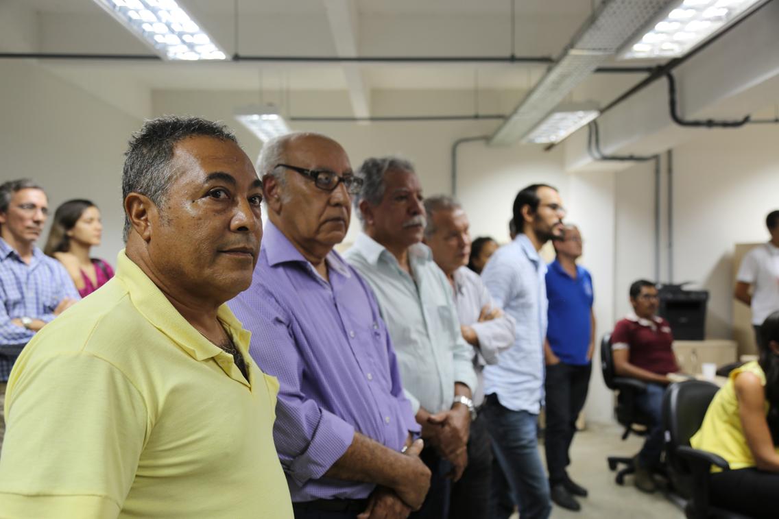 parte do público que assistiu a solenidade, seis homens estão em pé, olhando para o reitor