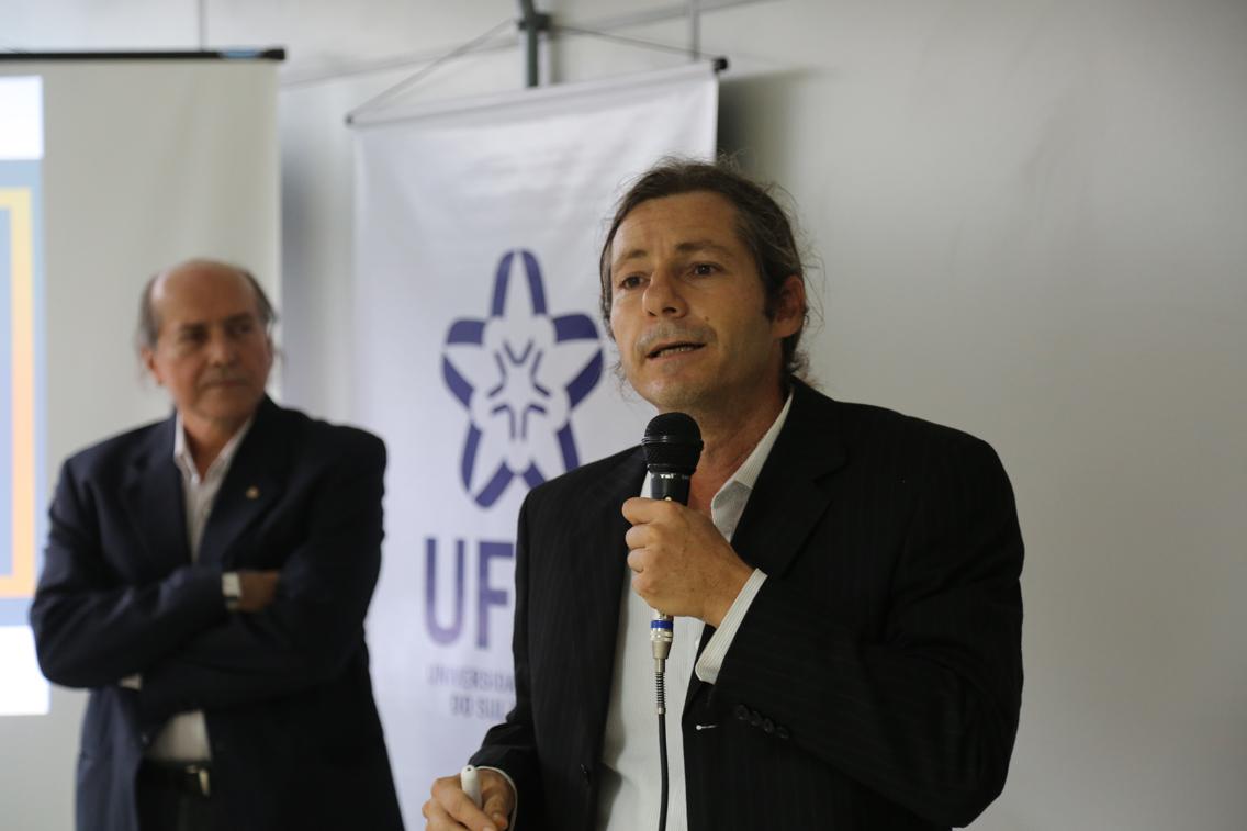 professor Daniel Piotto fala ao microfone; em segundo plano, em pé, o reitor da ufsb, Naomar Almeida Filho