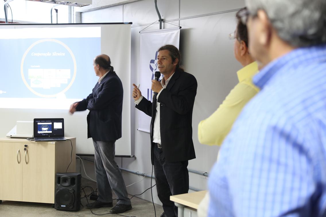 A fotos mostra em primeiro plano parte da audiência do evento; em segundo plano, o professor Daniel Piotto fala ao microfone, expondo dados projetados em uma tela; ao fundo, o reitor Naomar Almeida Filho observa e ajuda na projeção