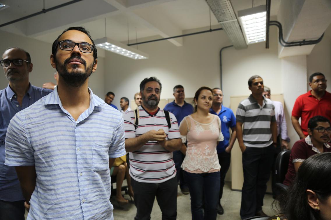 parte do publico que participou da cerimônia, em primeiro plano um homem jovem, de camisa padrão xadrez na cor azul; atrás e ao lado dele, dois homens com camisetas de listras horizontais e uma mulher com uma blusa em tons claros de rosa