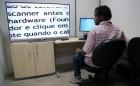 o aluno Uallas está sentado à direita de uma grande tela de tv, na qual estão aparecendo as palavras captadas pela lupa eletrônica