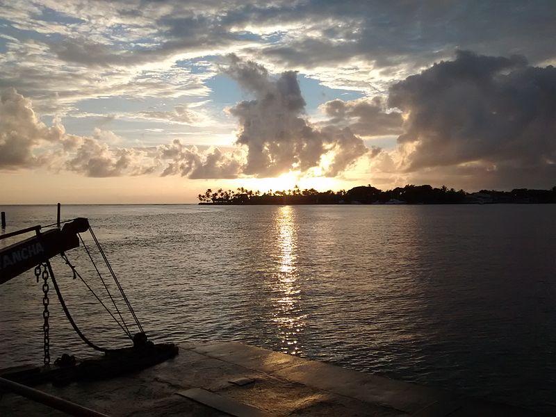 foto do por do sol no rio buranhém, com silhueta de faixa de terra no fundo da foto, e detalhe de um atracadouro no primeiro plano