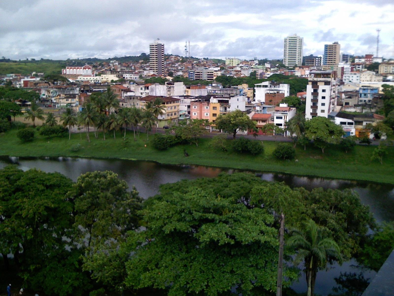 vista da cidade de Itabuna, com o rio Cachoeira no centro da imagem, copas de árvore no primeiro plano e prédios da cidade ao fundo