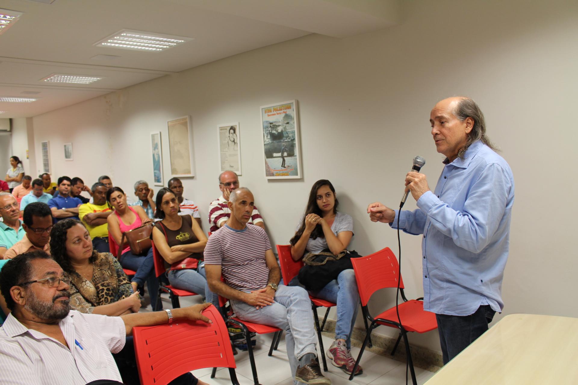 O reitor naomar, em pé à direita na imagem, fala ao microfone para a plateia, que está sentada em cadeiras dispostas em filas.